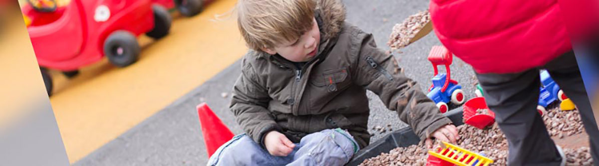 Child playing with sand in outdoor play area